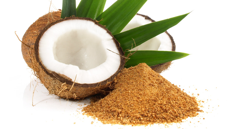 Cut open coconut next to pile of coconut sugar