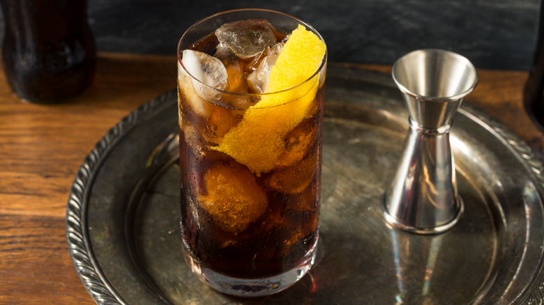 Glass of Fernet with citrus wedge on silver platter