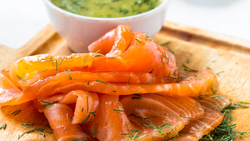 Gravlax covered in dill with mustard sauce in background