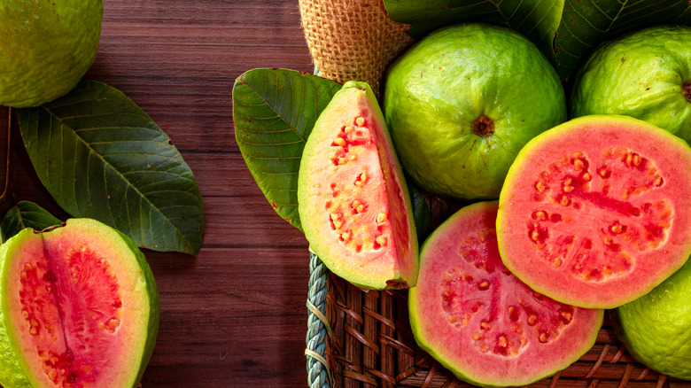 Whole and sliced guavas on a table