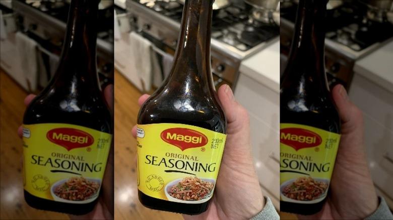 Hand holding maggi bottle