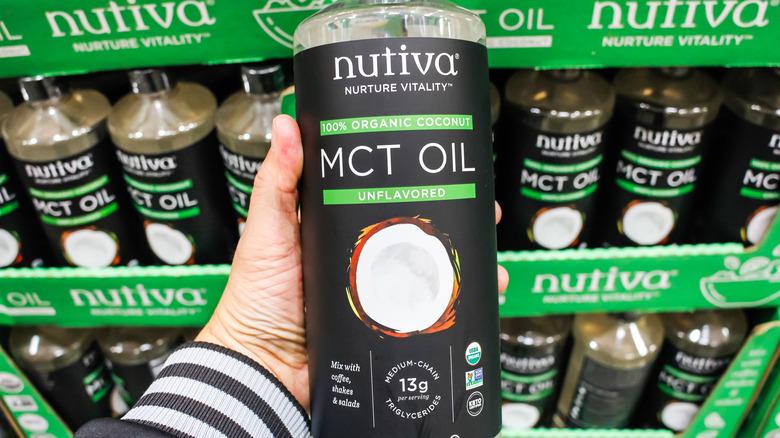 Hand holding a bottle of Nutiva MCT oil
