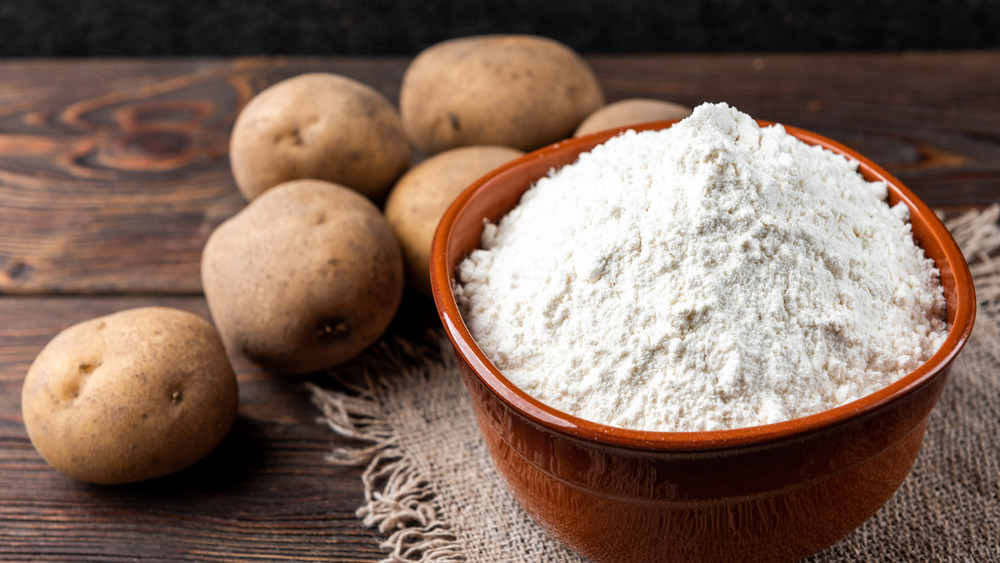 Potato starch with bowl on table with potatoes
