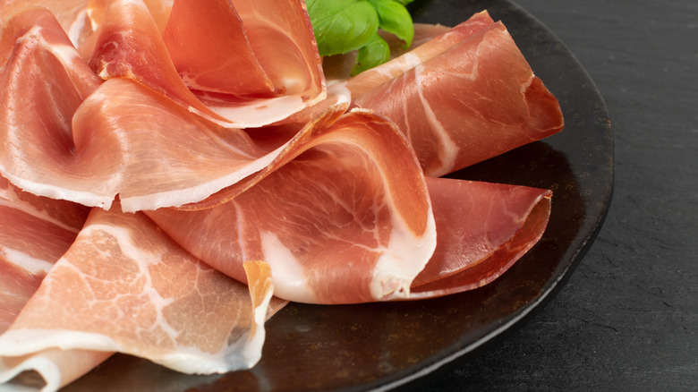 Thin slices of pink prosciutto on a plate