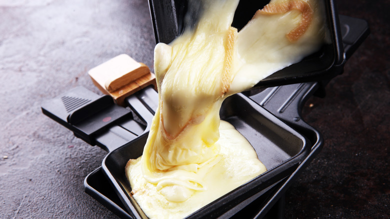melted raclette cheese scraped into black dish