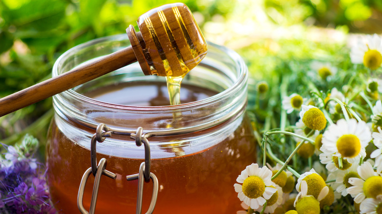 Jar of honey with honey spool and flowers