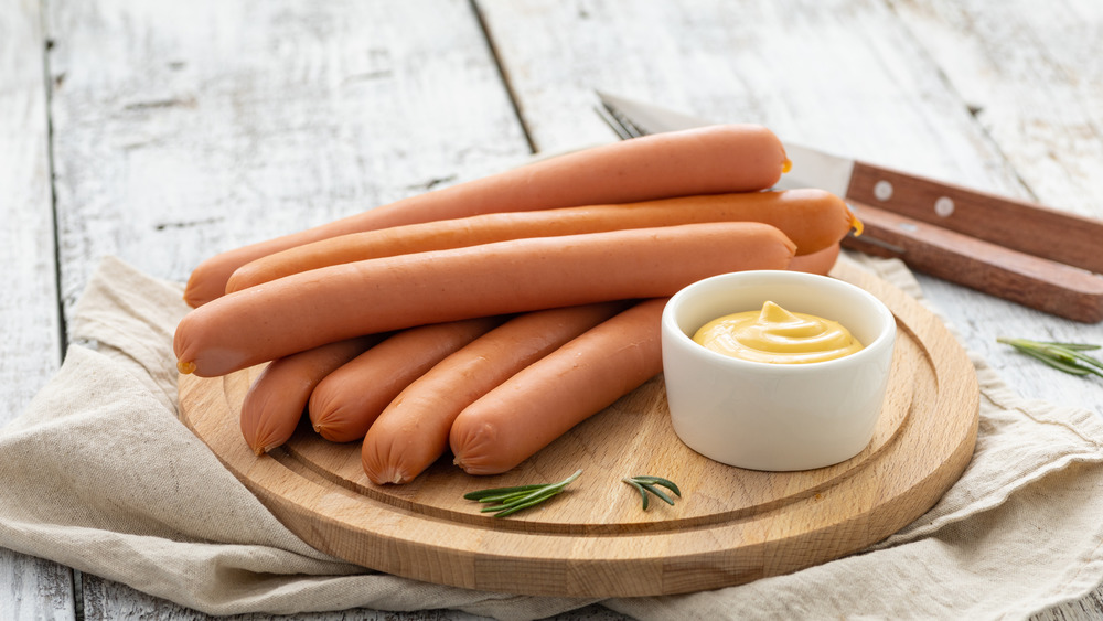 raw hot dogs on cutting board with mustard