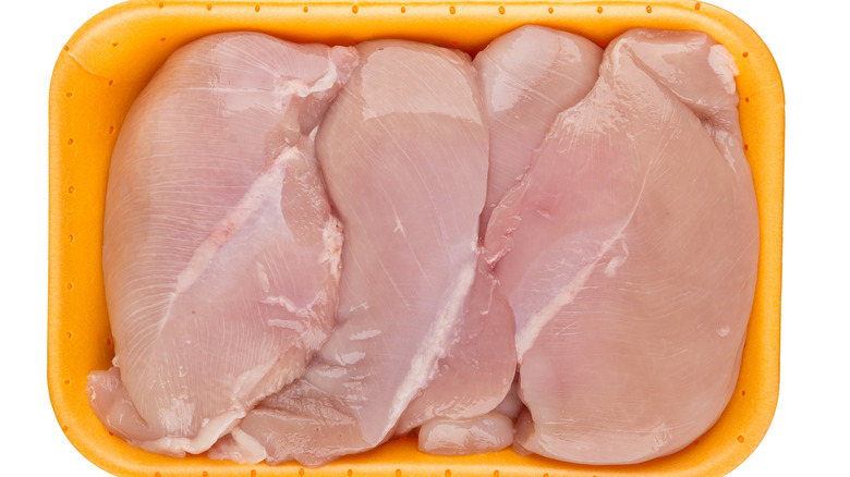 Raw chicken in yellow tray