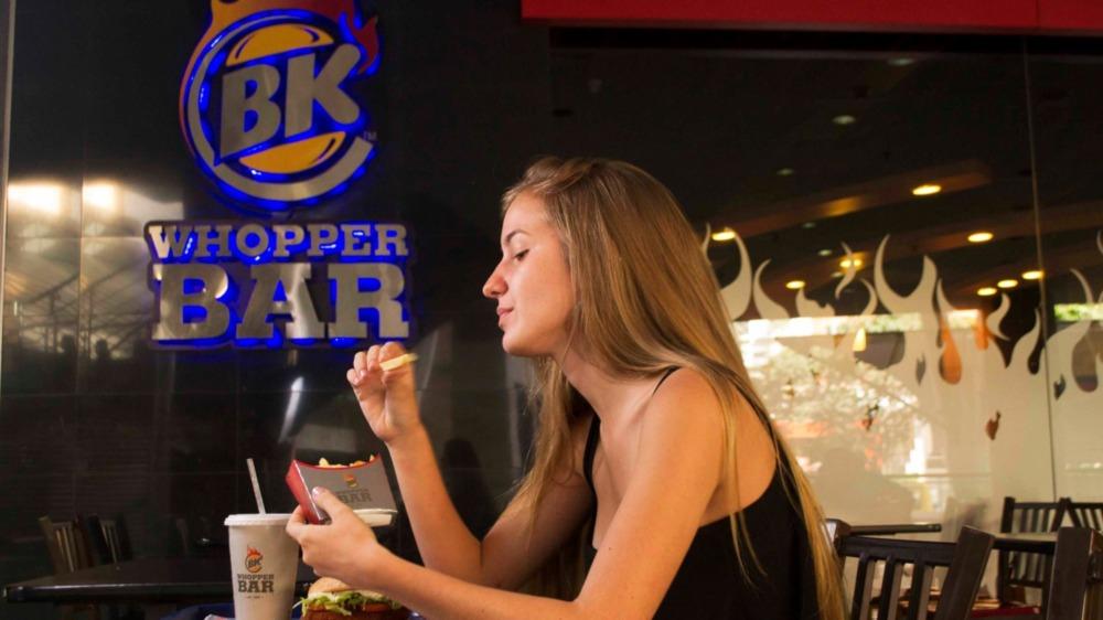 Girl sitting at Whopper Bar eating fries