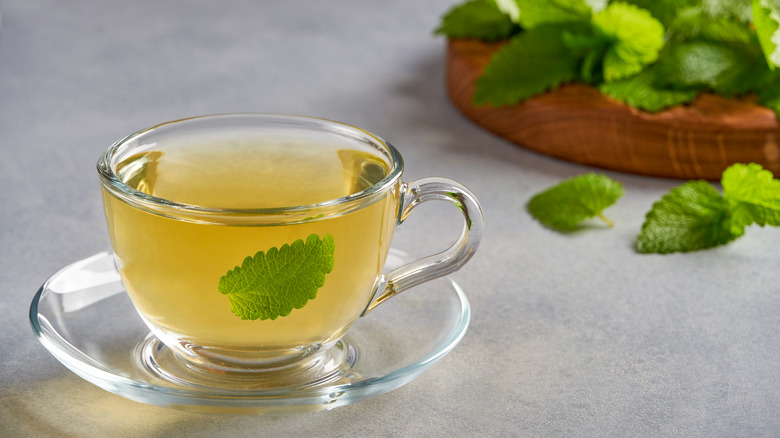 A tea cup with a leaf in it