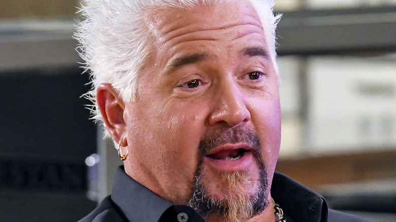 guy fieri seated at a table