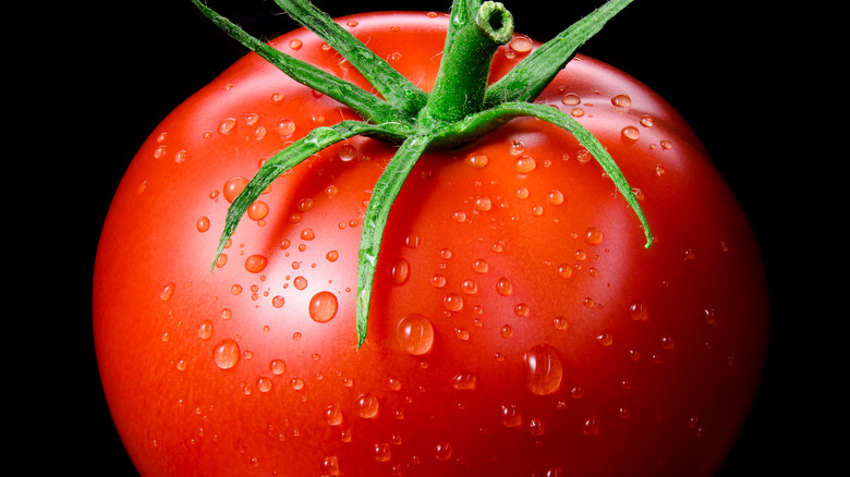 Closeup photo of red tomato with green stem
