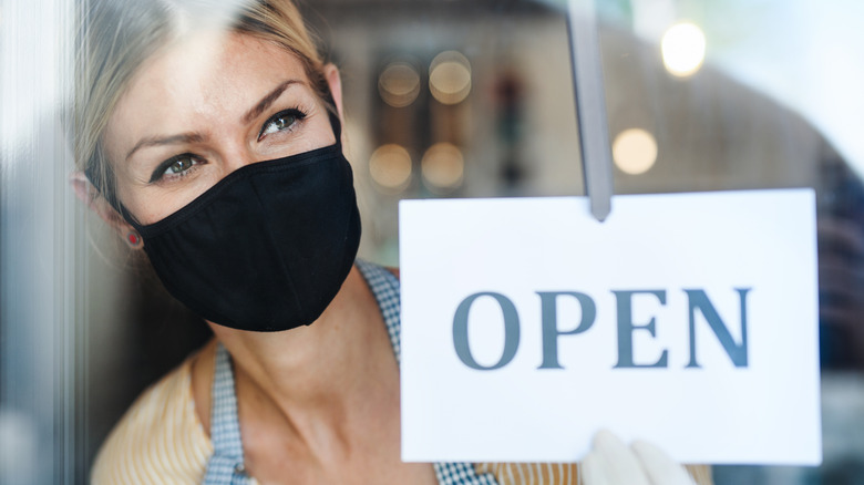 A woman at a retaurant wearing a mask