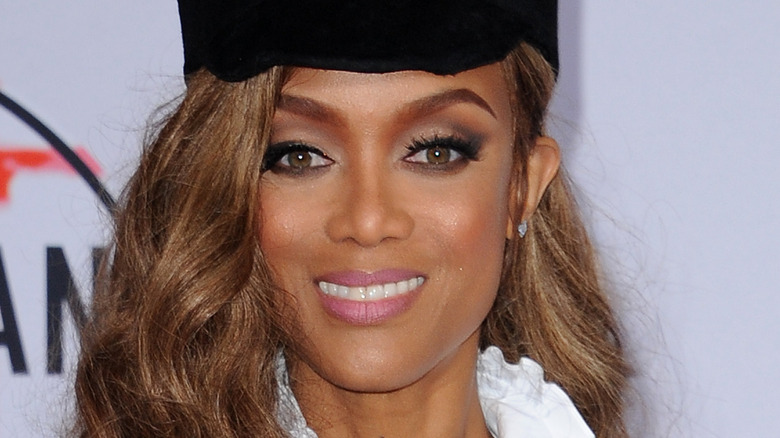 Tyra Banks wears a black hat and smiles