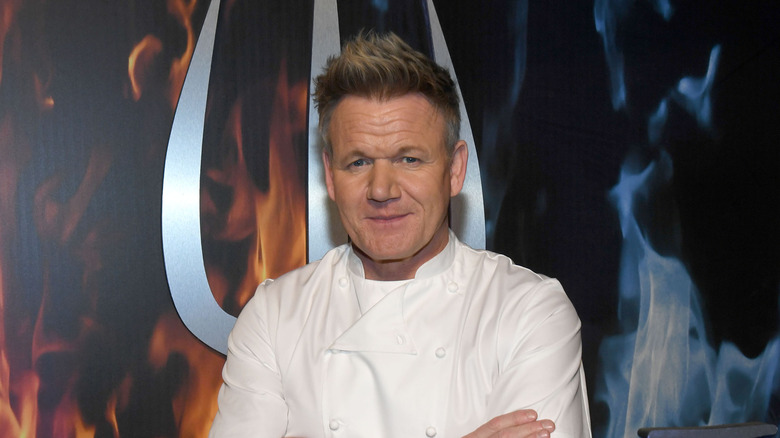 Gordon Ramsay posing in front of Hell's Kitchen sign