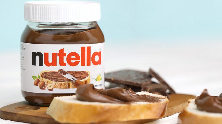Nutella jar alongside bread slices covered with the spread