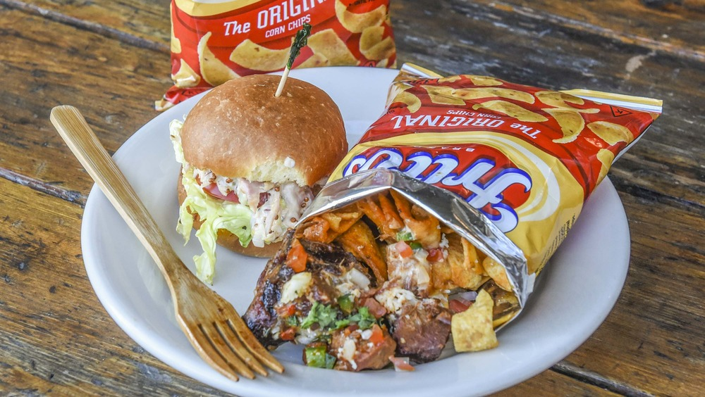 Fritos pie in a bag on a dish with a burger