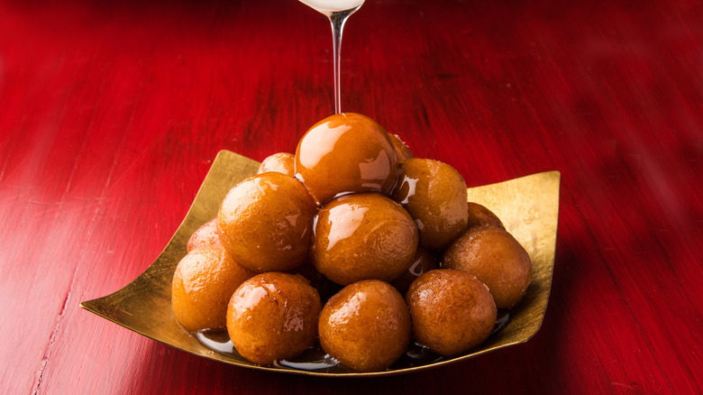 Gold plate of gulab jamun with syrup being poured over