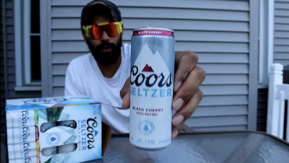YouTube reviewer holding up can of Coors Seltzer