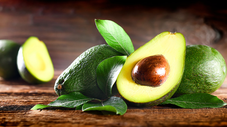 Avocados on a brown table.