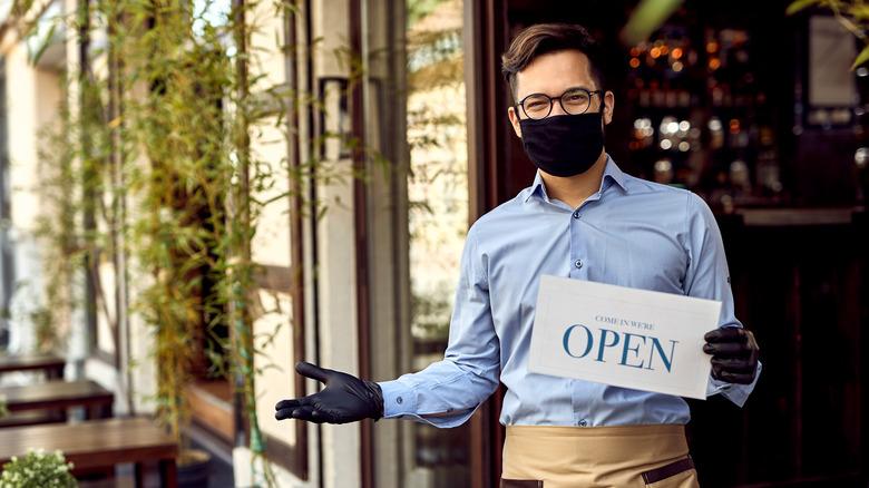 Masked server at outdoor restaurant