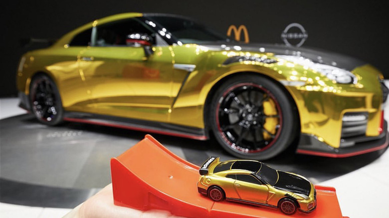 Holding a McDonald's toy GT-R in front of the McDT-R
