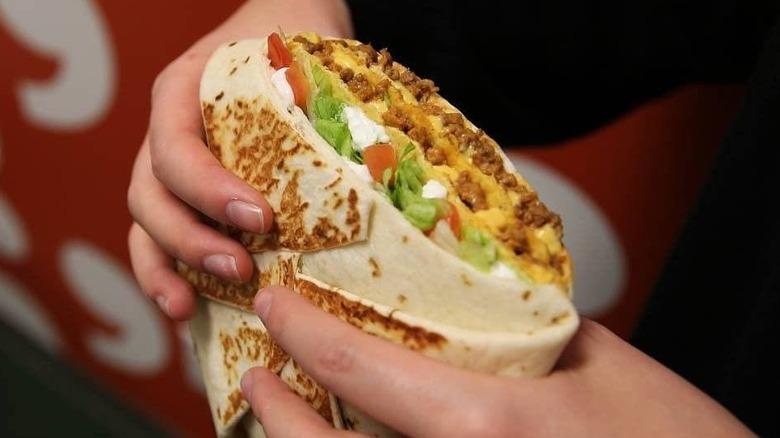 A Taco Bell Granda Crunchwrap in hand