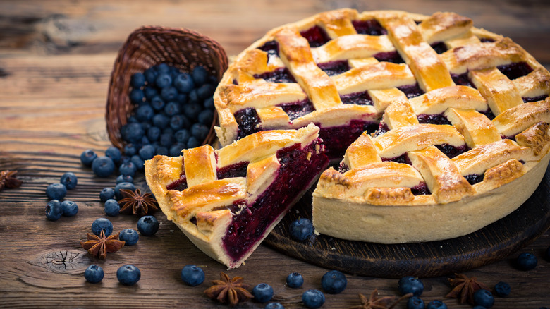 Blueberry pie with fresh blueberries on wooden surface