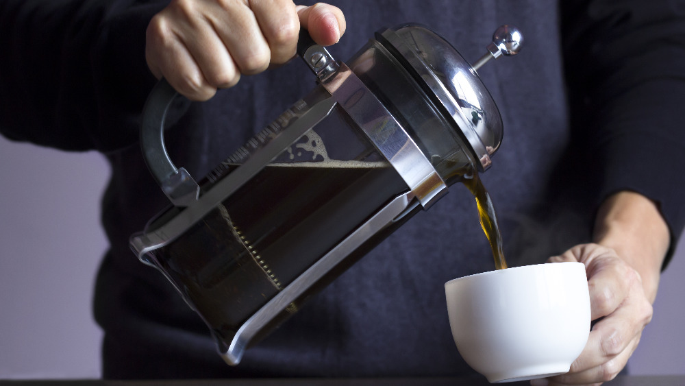 person pouring coffee from a French press