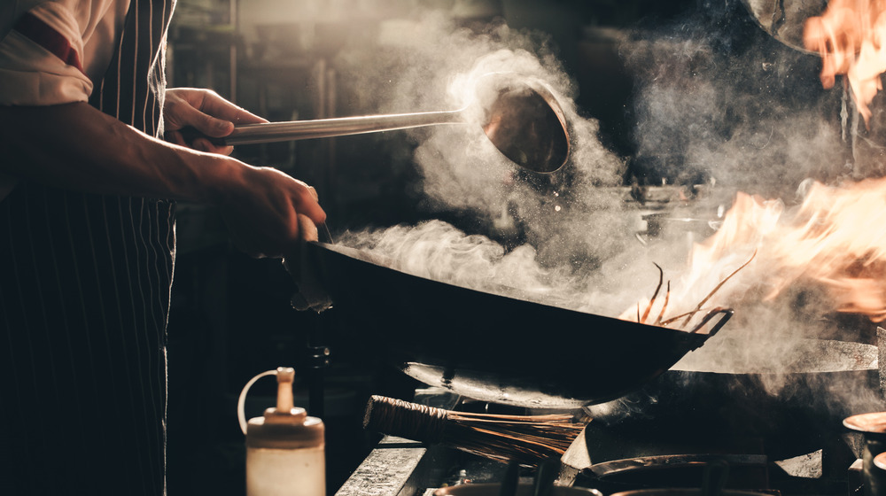 Chef using a steaming wok in a kitchen