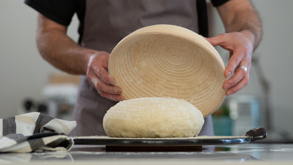 Man holding bowl over bread dough