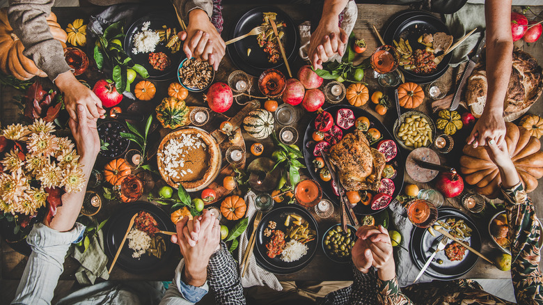 Thanksgiving table with turkey and sides, holding hands