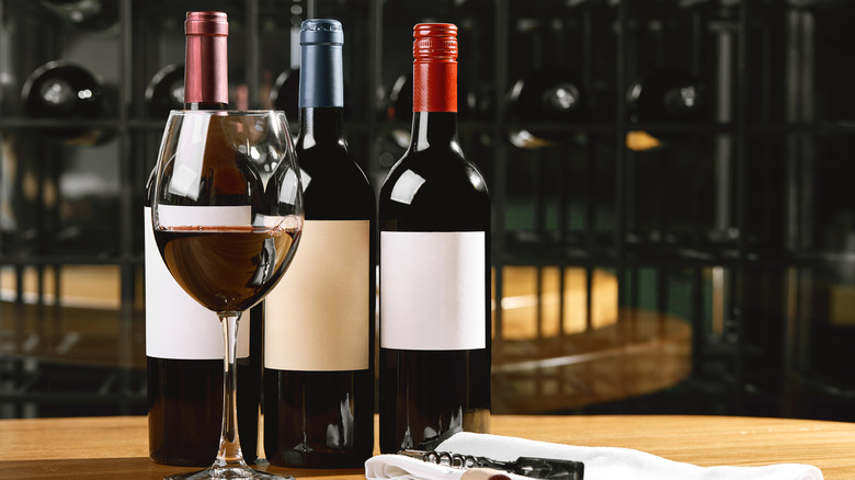 Three wine bottles and glass of red wine