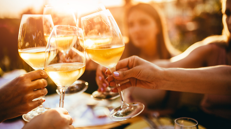 Glasses of white wine clinking