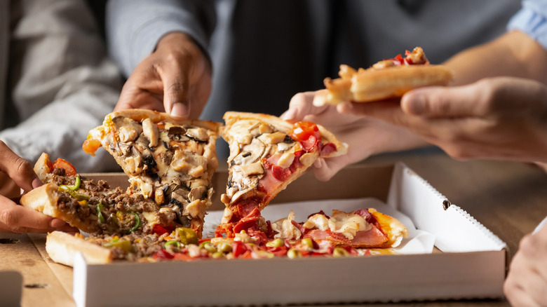 People eating pizza from a box