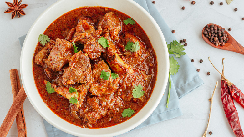 White bowl full of meat and red sauce next to spices