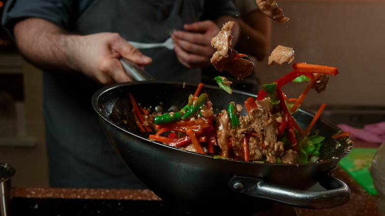 Tossing vegetables in a wok