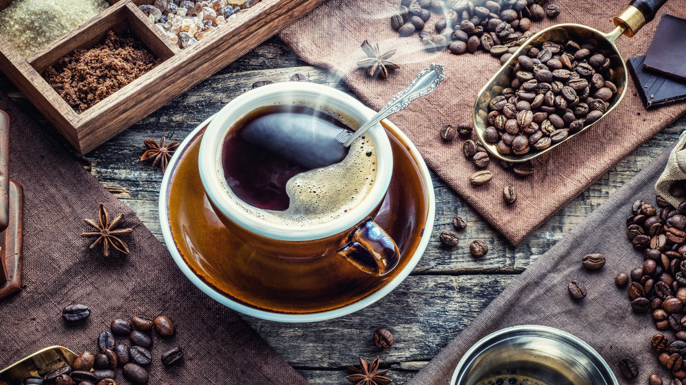 Cup of coffee with beans and spices