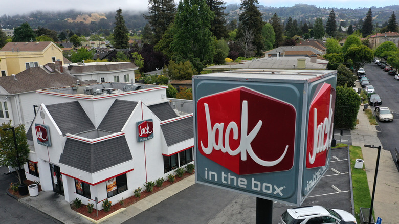 Jack in the Box sign and building against backdrop of trees