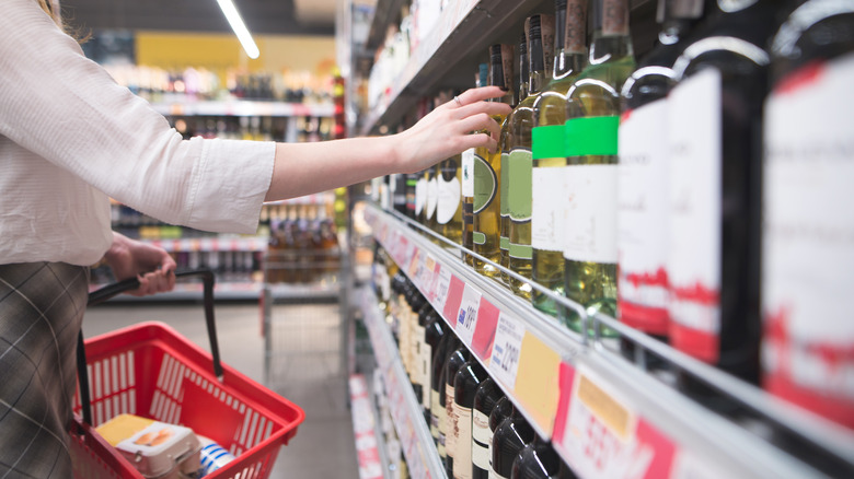 Person picking wine off the shelf