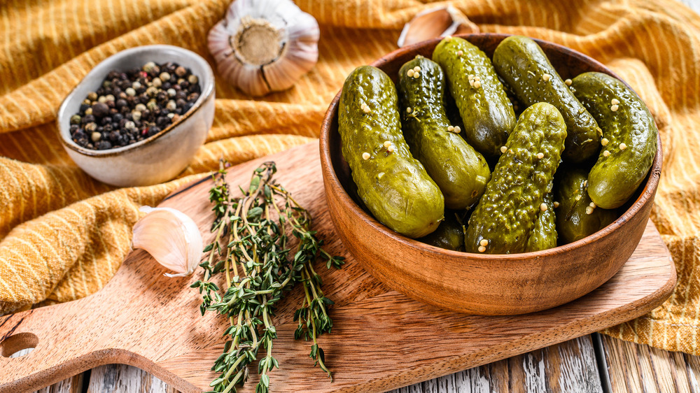 Bowl of pickles on cutting board next to rosemary sprigs