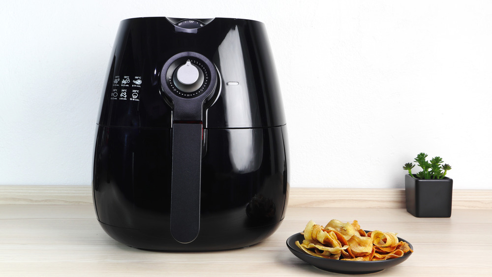 Air fryer on a countertop with a plate of chips