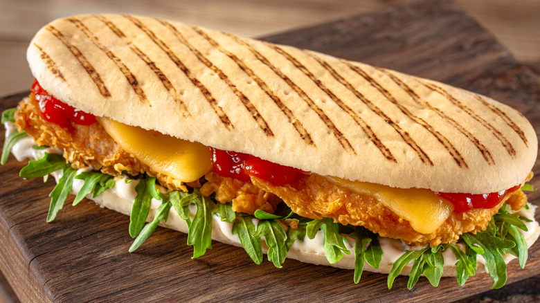 Panini sandwich with sauce, chicken, and salad