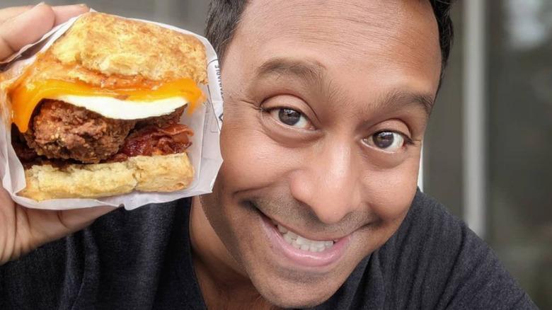 Ali Khan holding a sandwich