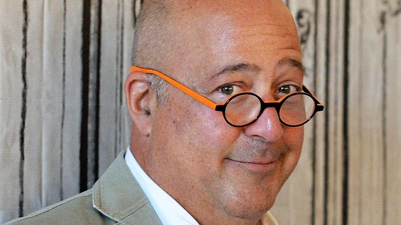 Andrew Zimmern in orange-framed glasses