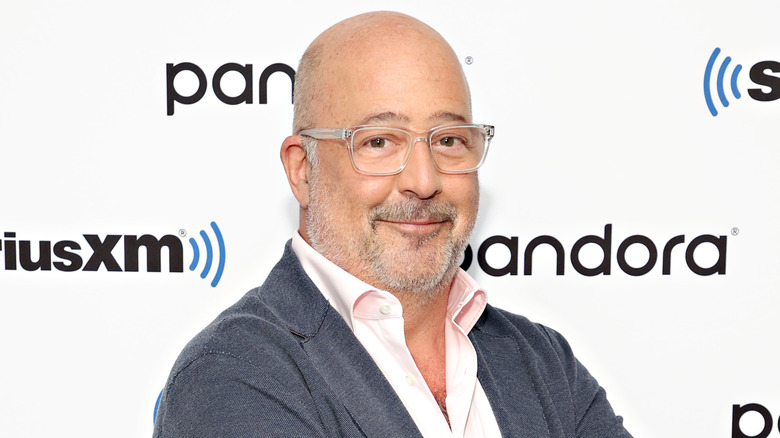 Andrew Zimmern smiles with glasses in close-up