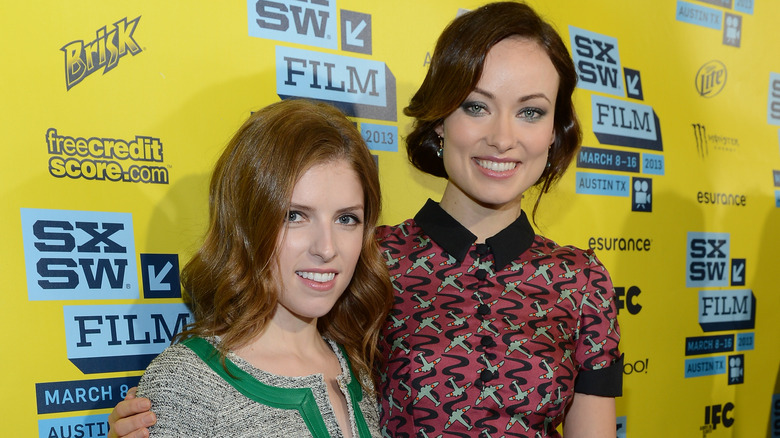 Anna Kendrick smiles in green with Olivia Wilde in a printed dress