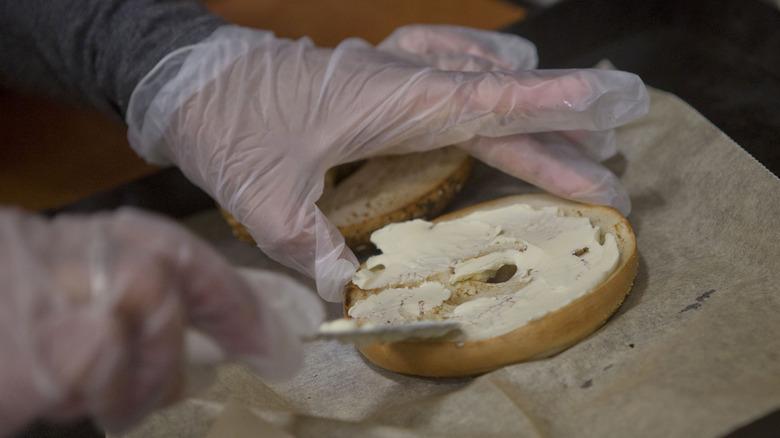 Spreading cream cheese on bagel