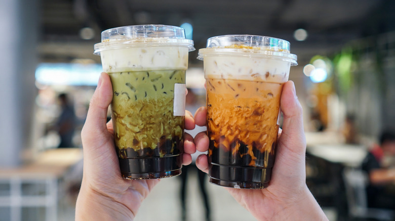 Two hands holding up Boba tea