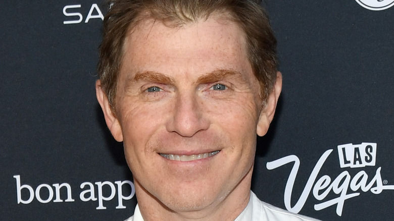Bobby Flay wearing a chef's shirt, standing against a black and white step and repeat